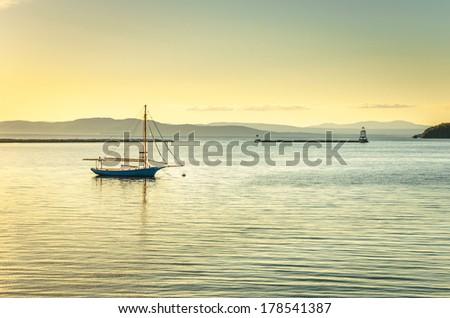 Anchored Sailing Boat at Sunset - stock photo