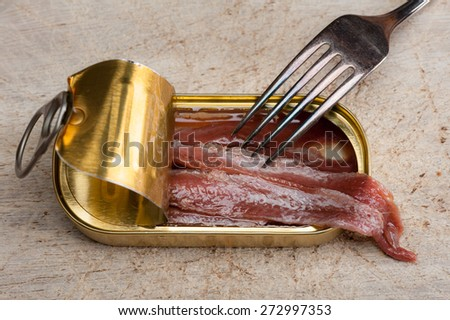 Anchovies in an opened tin can on wood, with a fork - stock photo