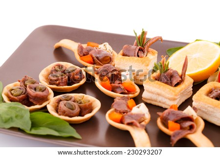 Anchovies in pastries, lemon and basil on brown plate. - stock photo