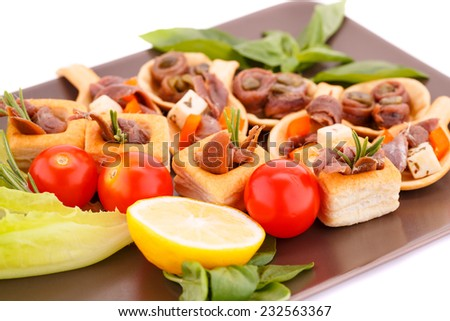 Anchovies in pastries, lemon, tomato, lettuce and basil on brown plate. - stock photo