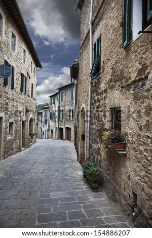 Ancient alleyway with dramatic sky. (Montalcino. Tuscany, Italy)  - stock photo