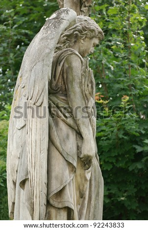 ancient angel statue in old christian cemetery - stock photo
