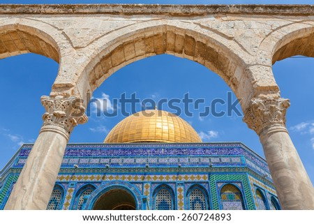 Ancient arch and Dome of the Rock Mosque under blue sky in Jerusalem, Israel. - stock photo