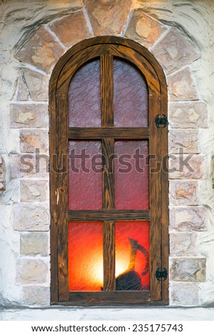 ancient arch window in a stone wall with a light and silhouette of the jug - stock photo