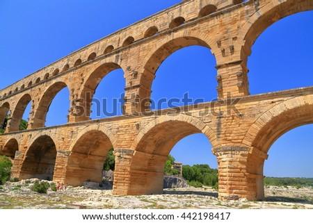 Ancient arches of Pont du Gard aqueduct near Nimes, France - stock photo