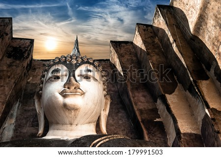 Ancient architecture of Buddhist temples in Sukhothai Historical Park. Statue of  Buddha Phra Achana at Wat Si Chum Temple under sunset sky. Thailand - stock photo