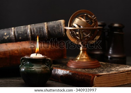 Ancient astrology. Old astrology globe and books near lighting candle - stock photo