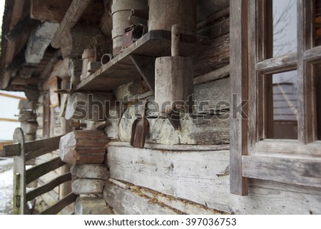 Ancient authentic ukrainian wooden hut, wall with window and other retro self-made household - stock photo