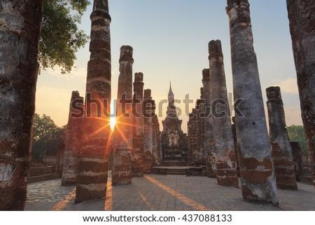 Ancient  big buddha image and ruin city at Sukhothai historical park ,UNESCO world heritage site, Sukhothai, Thailand, during sunset. - stock photo