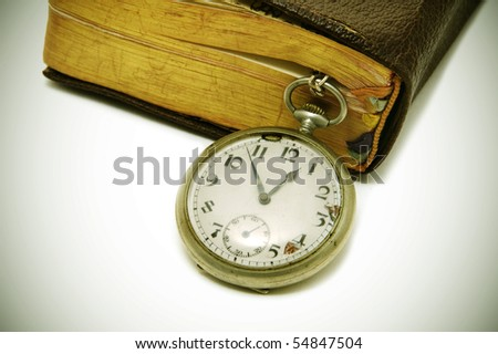 ancient book and pocket watch on a degraded background - stock photo