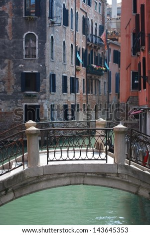 Ancient bridge on the water canal and old houses in background in Venice, Italy - stock photo