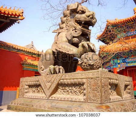 Ancient bronze lion and red chinese paviliones in famous Lama Temple (Beijing, China) - stock photo
