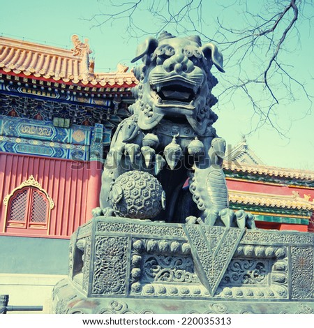 Ancient bronze lion and red chinese paviliones in famous Lama Temple (Beijing, China), instagram effect, square toned image - stock photo