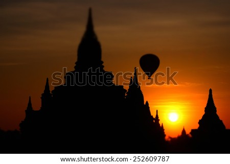 Ancient Buddhist Pagoda silhouette and balloon flying at amazing sunrise. Architecture of old Temples at Bagan Kingdom, Myanmar (Burma) travel landscapes and destinations. Tilt shift effect - stock photo