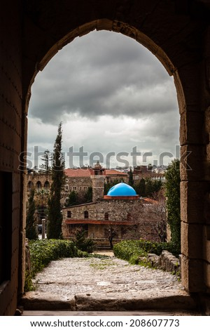 Ancient castle doorway arch in Byblos Lebanon with a blue dome mosque framed in door. Taken on grey overcast cloudy day. / Castle Gate Archway and blue Mosque. - stock photo
