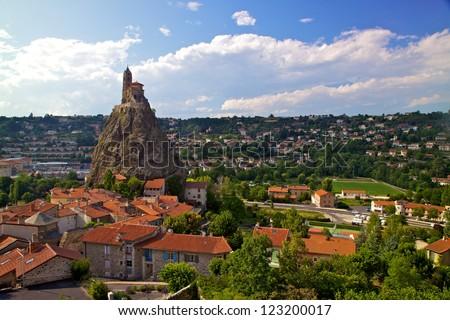Ancient Chapel Saint Michel de Aiguilhe standing at a very steep volcanic needle (Le Puy en Velay, France) - stock photo