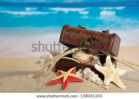 Ancient chest with sea cockleshells and a rope on sand - stock photo