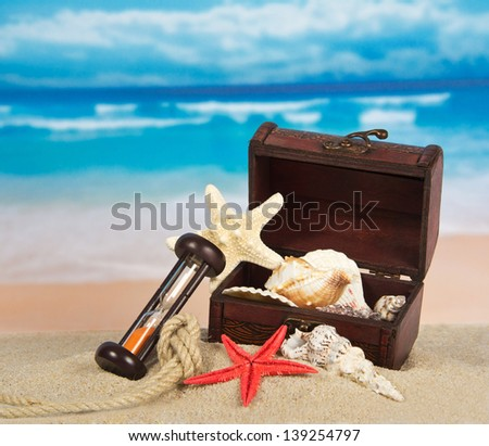 Ancient chest with sea cockleshells, hourglasses and a rope on sand - stock photo