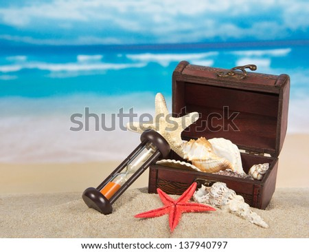 Ancient chest with sea cockleshells, hourglasses on sand - stock photo