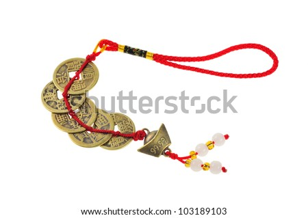 Ancient Chinese coins connected by red strings and knots and decorated with small jades. - stock photo