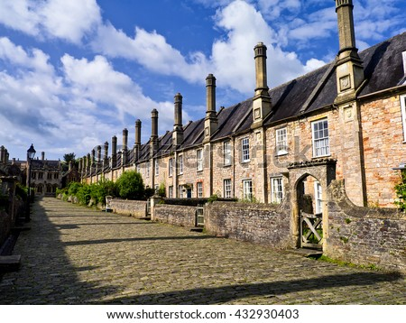 Ancient cobbled street; ancient houses in cobbled street in English cathedral town, under summer sky  - stock photo