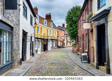 Ancient cobbled streets lined with shops and houses at Elm Hill in Norwich, Norfolk - stock photo