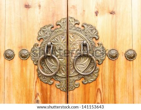 ancient door knocker on a wooden door - stock photo