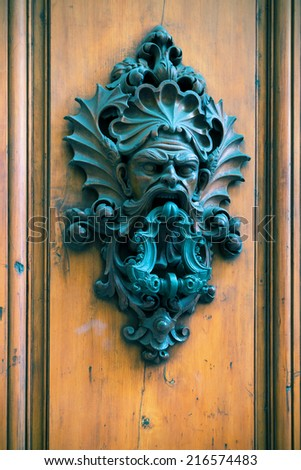 Ancient door knocker on a wooden door in Florence, Italy  - stock photo