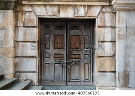 Ancient double wooden doors with lock and chain - stock photo