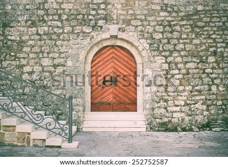 Ancient entrance to the historical building of the citadel in the old town of Budva, Montenegro. Heavy brown wooden door with black metal bar, old rough stone wall and marble stairs in front - stock photo