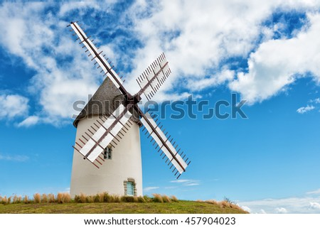 ancient european windmill restored on the top of a hill - stock photo