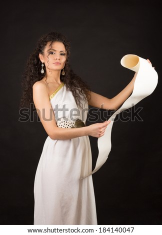 Ancient godness in a white greece toga on a black background holding a scroll - stock photo