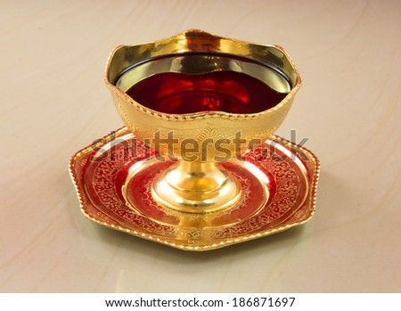Ancient golden chalice with red wine on a marble table. blood of Christ - stock photo