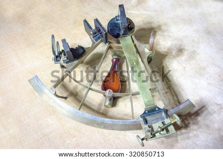 Ancient GPS navigator. Navigational instrument. Antique polished brass sextant over neutral background - stock photo