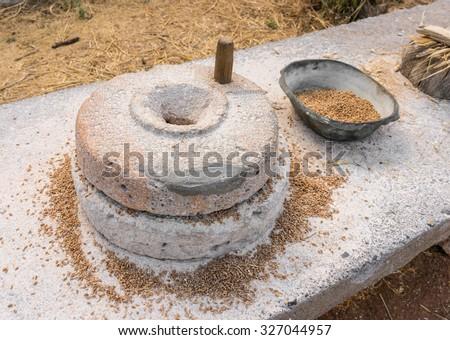 Ancient grain hand grinding millstones. - stock photo