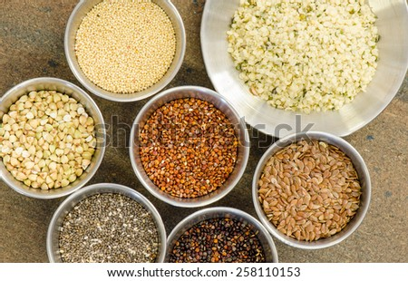 Ancient grains and healthy organic edible seeds in round stainless steel containers - stock photo