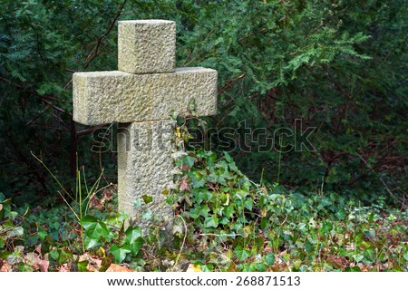 ancient grave stone cross from roughly hewn granite in evergreen plants with copy space - stock photo