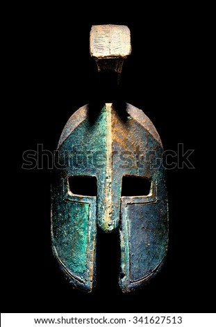 Ancient greek Spartan style helmet isolated on a black background, studio shot. - stock photo