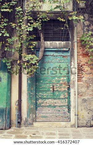 ancient green wooden door in Venice, Italy - stock photo
