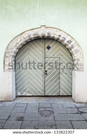 Ancient green wooden gate with arch in old building facade. Tallinn, Estonia - stock photo