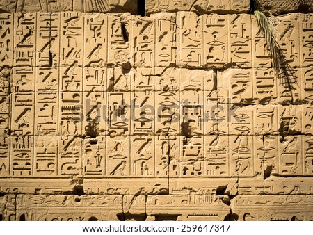 Ancient hieroglyphs carved on the stone wall of the Egypt landmarks. Textured background with a symbols of egyptian hieroglyph script. - stock photo