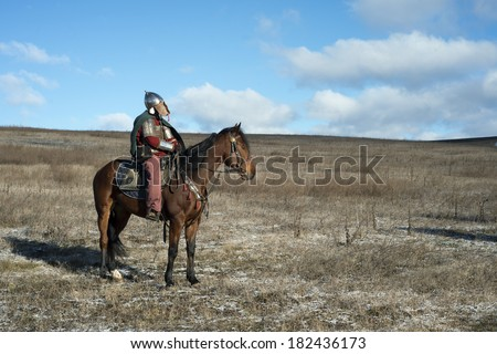 Ancient horseman in metal helmet observing steppe - stock photo