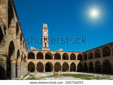 Ancient inn with clock tower in Akko - stock photo