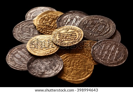 Ancient islamic golden and silver coins on black background, selective focus, closeup - stock photo