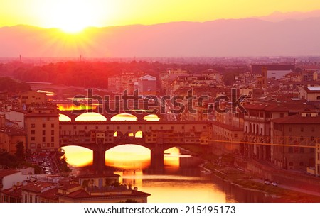 Ancient Italian bridge across Arno river in bright yellow sunset light, Florence, Europe, famous historical landmark, travel and tourism concept - stock photo