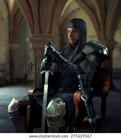 Ancient knight in metal armor sitting on a wooden chair in a palace - stock photo