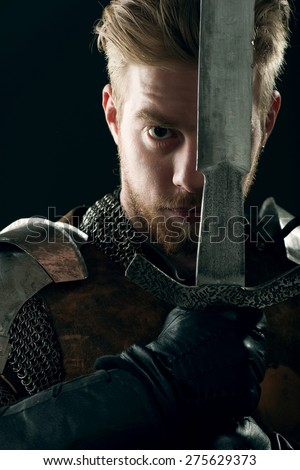 Ancient knight in metal armor with sword on gray background - stock photo
