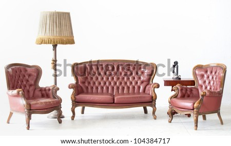 ancient leather sofa with lamp and telephone in white room. - stock photo