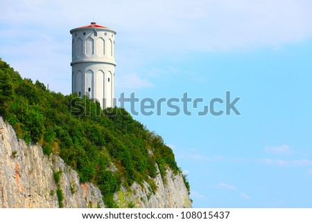 Ancient lighthouse  on a cliff over the Gulf of Trieste (Adriatic sea), Italy. - stock photo