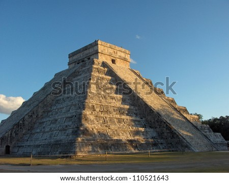 Ancient Mayan pyramid Chichen Itza in Mexico, Riviera Maya with blue skies above and grass field below, trees in background - stock photo